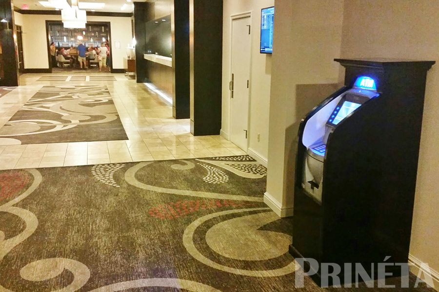 triton argo 12 atm machine with black wood cabinet in a hotel lobby