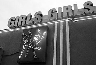 strip club light up sign reading girls girls