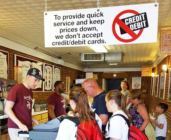 Sign in a store: To provide quick service and keep prices down we don't accept credit/debit cards