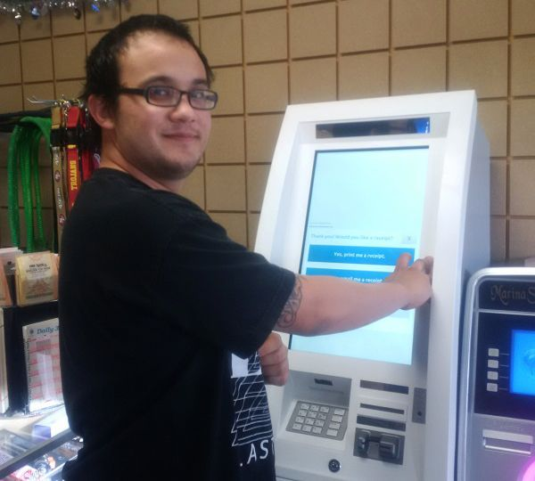 Customer withdrawing bitcoins from bitcoin ATM